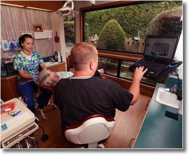 Dr. Wiles, a hygienist, and a patient review dental x-rays on a computer