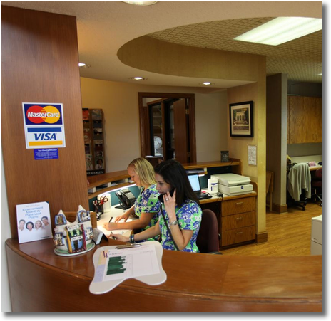 two young women work at the reception desk at Erwin Dental